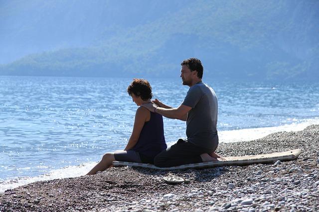 Muž so ženou sedia pri mori, pláž, masáž ramien, relax.jpg