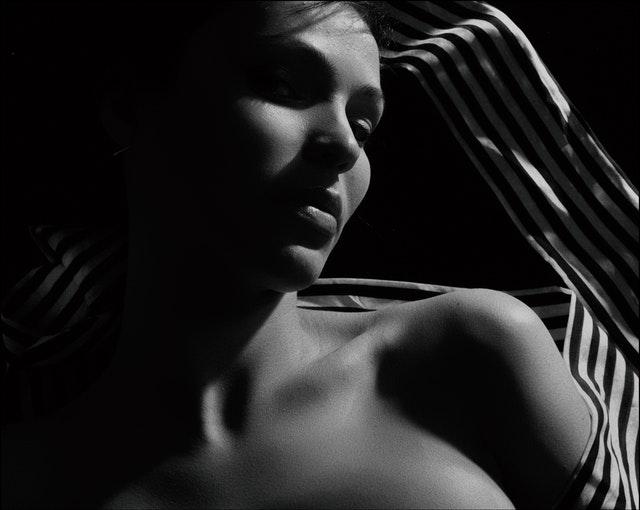 Polonahá žena v tieni omotaná pásikavou plachtou