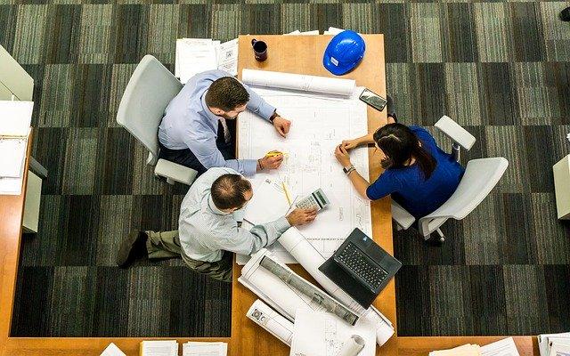 Traja ľudia sedia v kancelárii pri stole.jpg