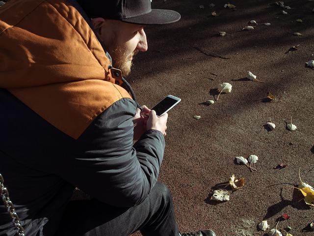 Muž sedí vonku a pozerá do telefónu